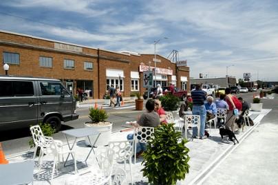 Em Wichita, estado de Kansas, o projeto estreitou uma avenida, ocupado duas pistas com ciclovia, um café ao ar livre, calçadas mais largas, floreiras e bancos. Foto de Ty Nigh/ Flickr