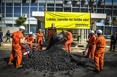 """Brasília-DF, 28 de agosto de 2013 Foto:Cristiano Costa/Greenpeace Uma tonelada e meia de briquete de carvão foi derramada em frente ao prédio do Ministério de Minas e Energia (MME), na manhã desta quarta-feira (28). Sujos dos pés à cabeça por uma poeira negra, ativistas abriram uma faixa com a mensagem: """"Lobão, carvão no leilão não!"""". O protesto era um recado do Greenpeace ao ministro Edison Lobão, contra a volta do carvão ao leilão de energia A-5 – empreendimentos com início de operação em até cinco anos –, que acontece nesta quinta-feira, 29."""