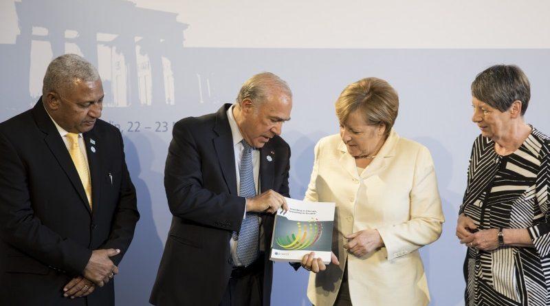 O secretário-geral da OCDE, Angel Gurría, entrega o relatório sobre crescimento econômico e ação climática à chanceler alemã Angela Merkel, que presidirá a próxima cúpula do G20 em julho (crédito: Axel Schmidt/OECD/Flickr - CC BY-NC 2.0)