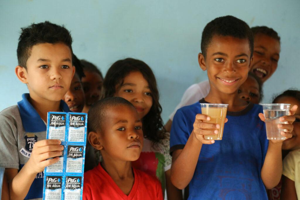 """Crianças em Chapada do Norte atendidas pelo programa. Os copos mostram o """"antes"""" e o """"depois"""" do uso do sachê. Foto: Jorge Novais/ Caixa Alta"""